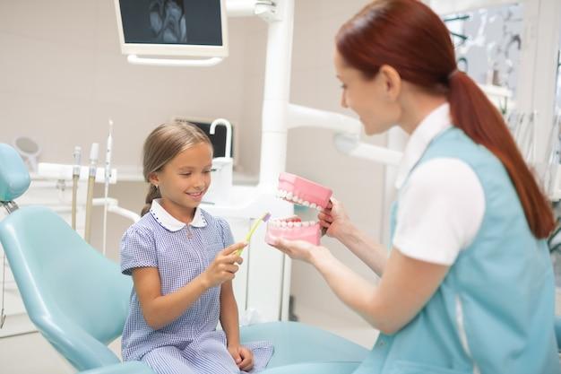 Девушка держит зубную щетку. улыбающаяся милая девушка держит зубную щетку и чистит зубы на модели зубов