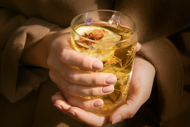 Girl holding a transparent cup of tea with herbs.