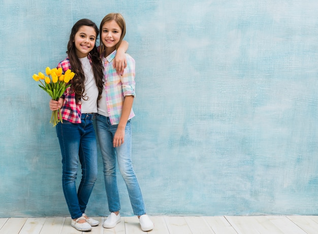 Girl holding tulips in hand standing with her female friend against blue wall