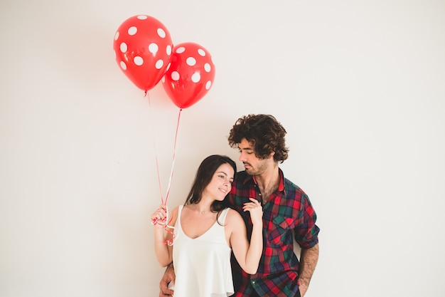 Girl holding two balloons as she rests her head on her boyfriend's chest