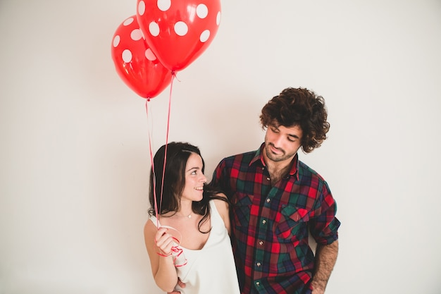 Girl holding two balloons with her boyfriend next to