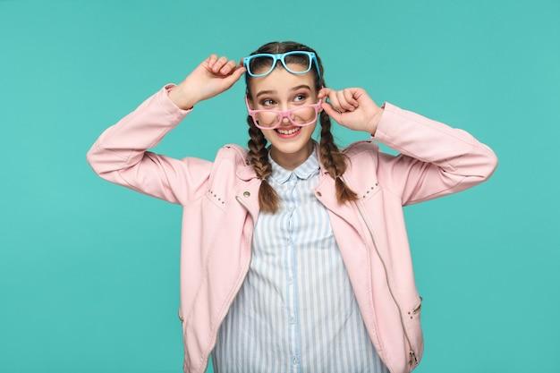 Девушка держит два синих и розовых очков и смотрит в сторону с зубастой улыбкой