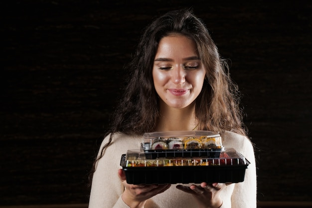 검은 바탕에 두 개의 초밥 상자를 들고 소녀