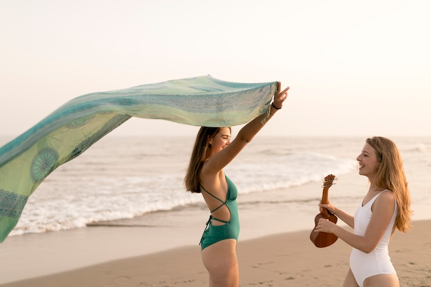 Girl holding ukulele looking at her friend holding green scarf at beach