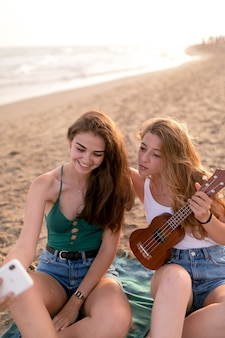 Girl holding ukulele taking selfie with her friend at beach