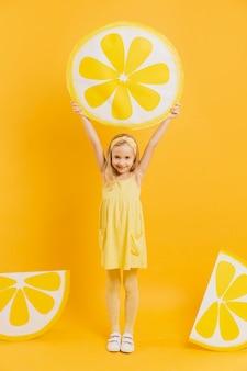 Девушка держит украшение ломтик лимона