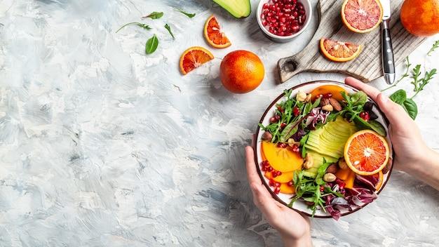 Девушка держит веган, детокс миску будды с фруктами и овощами, сбалансированное питание. место для текста. вид сверху.