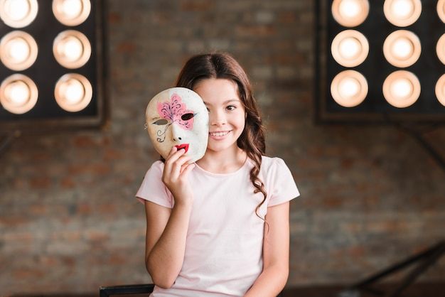 Girl holding venetian mask in her hands in front of stage light