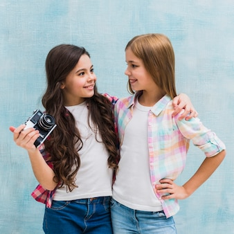 Girl holding vintage camera in hand looking at her female friend against blue wall