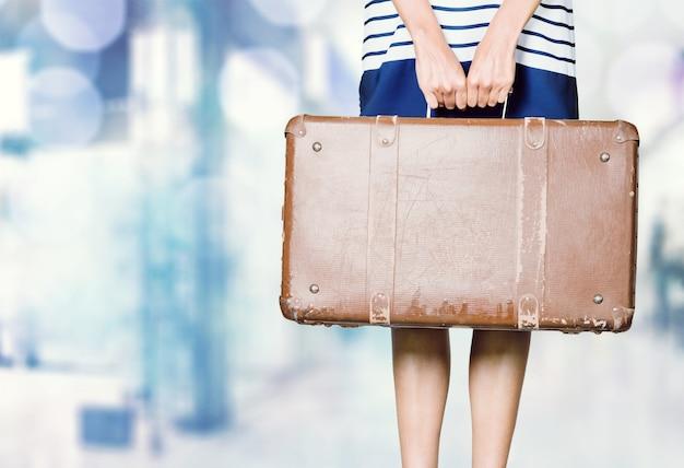 水色の背景にヴィンテージスーツケースを保持している女の子