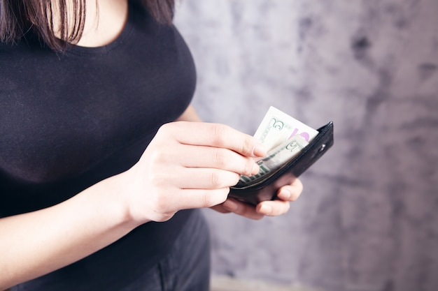 Girl holding a wallet in her hands and taking money on a gray background