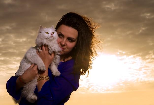 Girl holding white cat at sunset