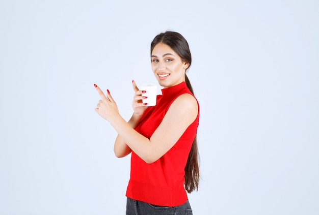 Girl holding a white coffee cup and pointing at it.