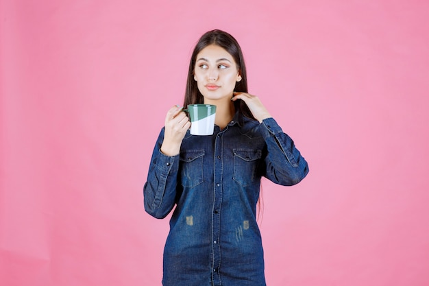 Girl holding a white green coffee mug and smelling