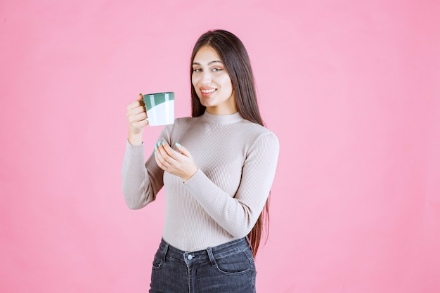 Girl holding a white green color coffee mug and feeling positive