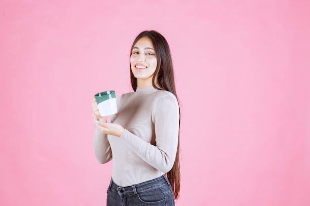 Ragazza che tiene una tazza da caffè di colore verde bianco e si sente positivo
