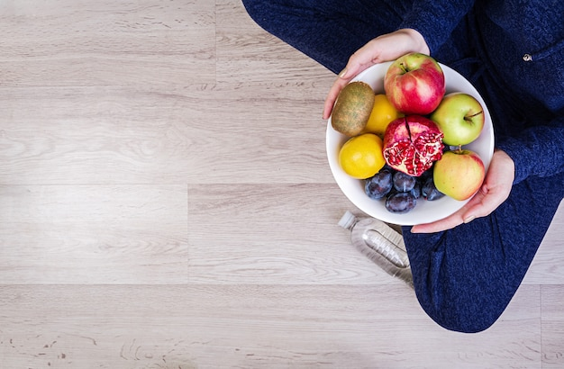 Girl holding white plate with apples, plums, kiwi and pomegranate. healthy eating.
