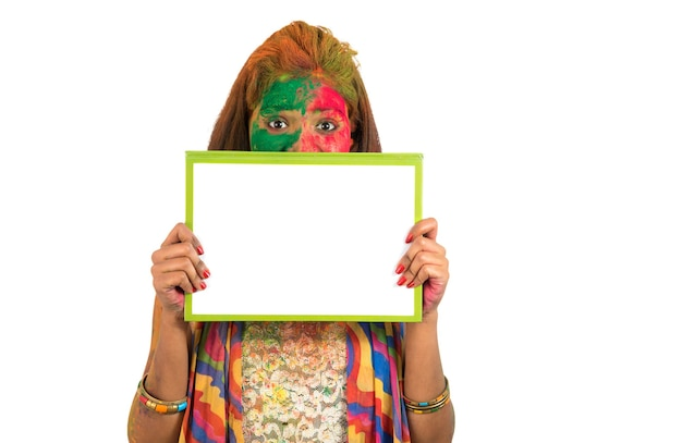 Girl holding a white signboard with face painted with color in festival of colour holi. isolated portrait
