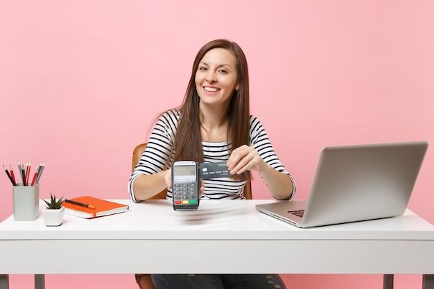 무선 현대식 은행 결제 단말기를 들고 있는 소녀는 분홍색 배경에 격리된 pc 노트북으로 책상에서 신용 카드 결제를 처리하고 획득합니다. 성취 비즈니스 경력 개념입니다. 공간을 복사합니다.