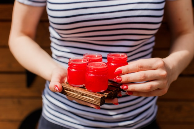 Girl holding a wooden board with 4 red shot drinks