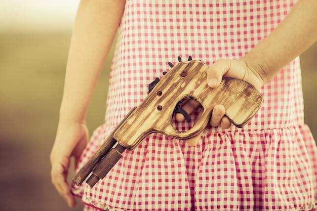 그녀의 뒤에 나무 총을 들고 소녀