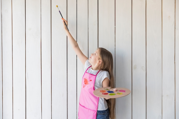 Girl holding wooden palette trying to paint on white plank wooden wall