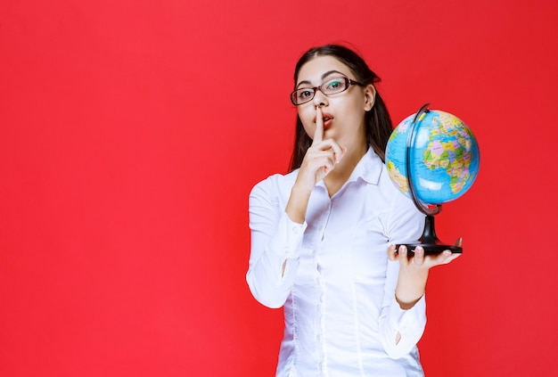 Girl holding a world globe and asking for silence.
