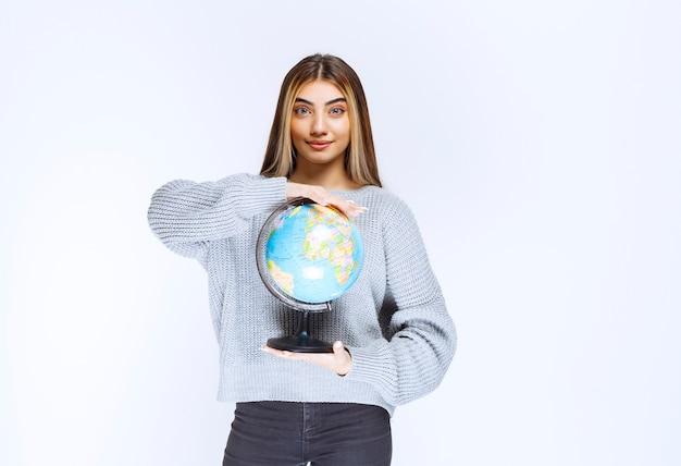 Ragazza che tiene un globo del mondo e lo promuove.