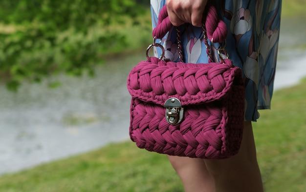 Девушка держит тканые модные фиолетовые сумки на открытом воздухе
