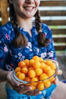 Девушка держит желтые сливы, выращенные в ее саду