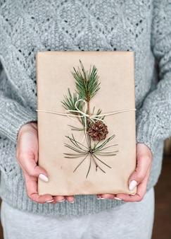 소녀는 원뿔 전나무 가지로 장식 된 공예 종이에 싸서 선물 책을 보유하고 있습니다.