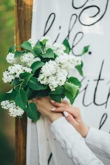 소녀는 그녀의 손에 하얀 라일락 꽃다발을 보유