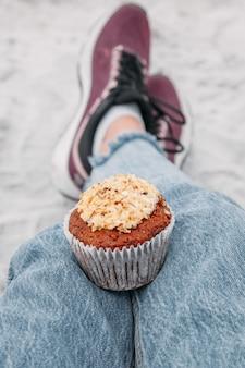 女の子は甘い食べ物とデザートのビーチのコンセプトでピクニック中にクリームとナッツとおいしいマフィンカップケーキを保持します