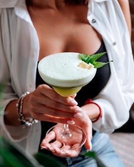 Девушка держит стакан зеленого напитка с пеной Бесплатные Фотографии