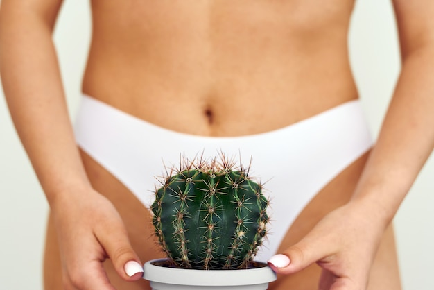Девушка держит большой кактус в области паха или бикини.
