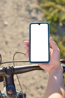 Девушка держит мобильный телефон верхом на велосипеде. макет