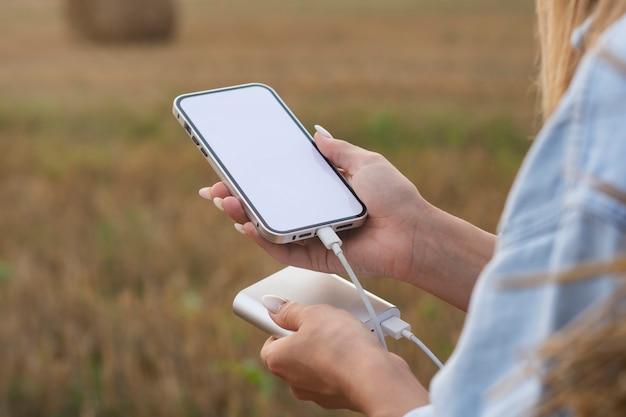 소녀는 손에 흰색 화면이 있는 스마트폰 모형을 들고 있습니다. power bank는 자연을 배경으로 전화를 청구합니다.