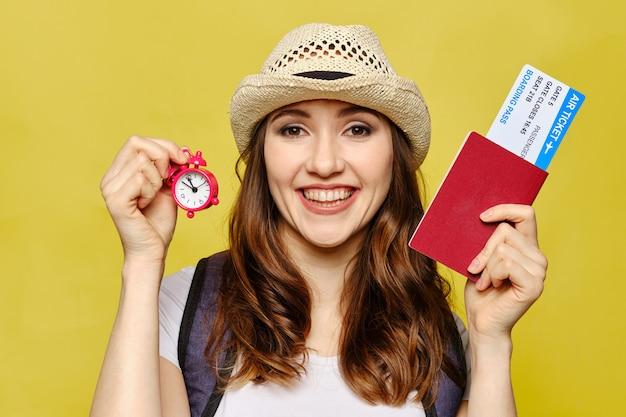 Девушка держит паспорт с билетами и часы на желтом фоне.