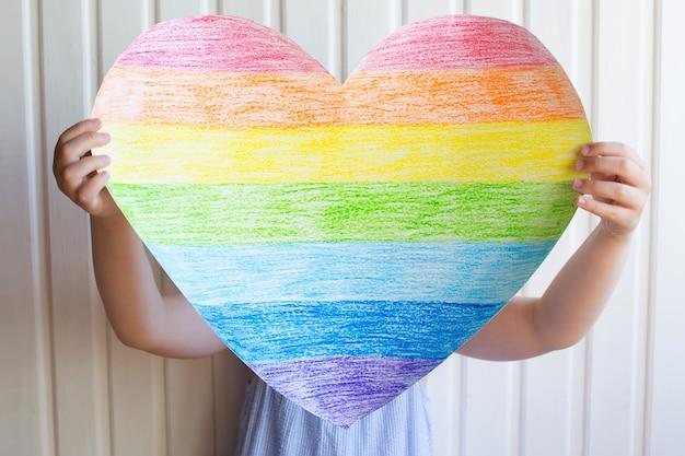 女の子は白い壁に彼女の手で虹の心を持っています