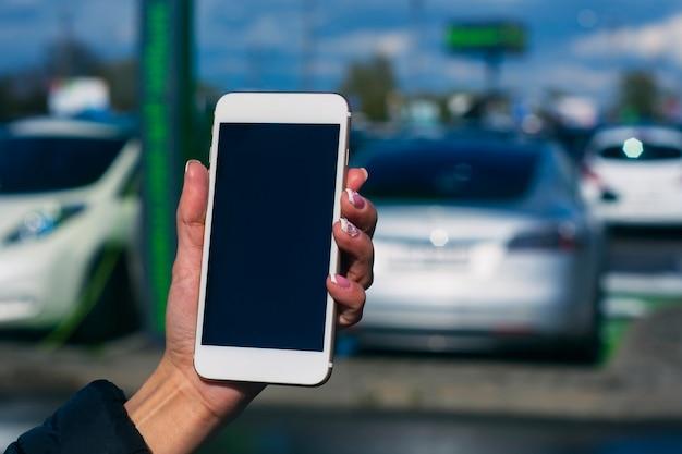 소녀는 그의 손에 스마트폰을 보유하고 있습니다. 충전소에서 전기 자동차의 배경에 대해 흰색 화면으로 전화를 조롱합니다.
