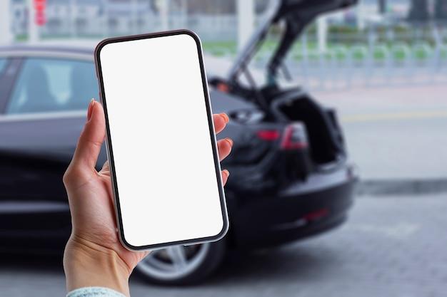 소녀는 그의 손에 스마트폰을 보유하고 있습니다. 자동차 배경에 흰색 화면이 있는 전화기를 조롱합니다.