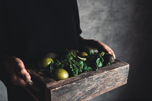 소녀는 빈티지 상자에 시금치, 아보카도, 라임 스무디를 보유하고 있습니다. 건강에 좋은 음식, 비건 채식, 친환경.