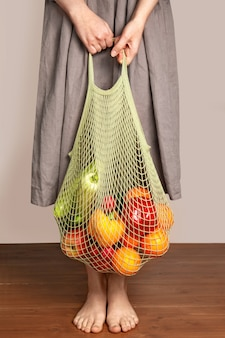 女の子は野菜と果物のひもバッグを保持しています。グリーンショッピングと良い栄養のコンセプト。製品の配送。環境を守ること。