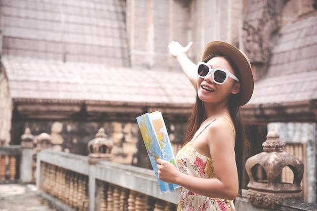 여자는 오래 된 도시에서 관광지도 보유하고있다.