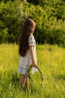 女の子は花の花輪を保持しています。背面図。日没