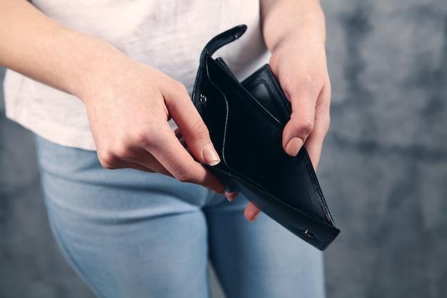 Девушка держит в руках пустой бумажник.