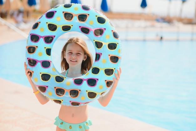 Девушка держит надувной круг для плавания у бассейна