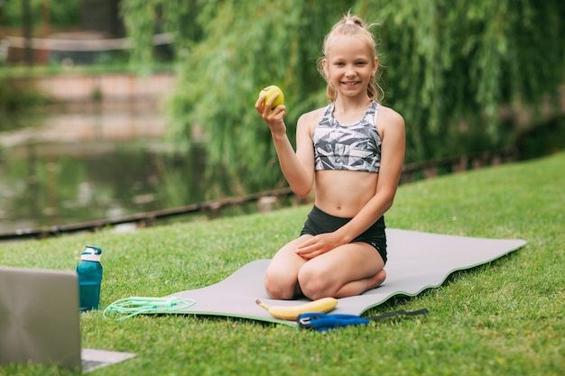 A girl holds an apple in her hand after undergoing an online outdoor training