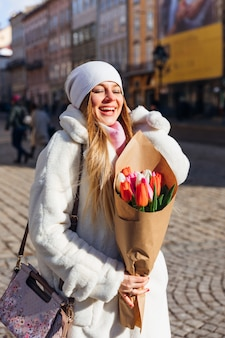 Girl holds beautiful bouquet of blooming pink red and white tulips