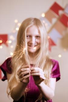 소녀는 벵골 조명을 보유하고 있습니다 - 행복한 크리스마스와 즐거운 휴일